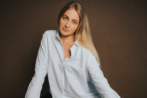 Aantrekkelijke blanke blonde vrouw in een wit overhemd poseren op een bruine muur