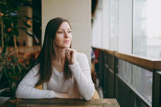 Aantrekkelijke blanke dromerige vrouw in lichte vrijetijdskleding die alleen zit in de buurt van een groot raam in de coffeeshop, ontspannend in het restaurant tijdens vrije tijd. jonge vrouw met rust in café. levensstijlconcept.