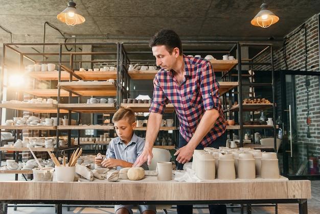 Aantrekkelijke blanke man en liitle schattige jongen kneden klei voor potten.