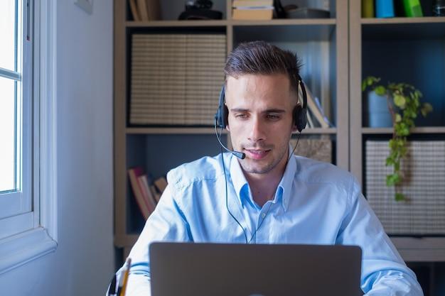 Aantrekkelijke blanke man zit in een thuiskantoor met een headset en neemt deel aan een educatief webinar met behulp van een laptop. videogesprek evenement met klanten of persoonlijk chatten met vriend op afstand concept