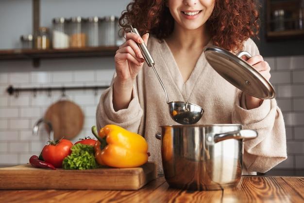 Aantrekkelijke blanke vrouw die kooklepel vasthoudt terwijl ze soep met verse groenten eet in de keuken thuis