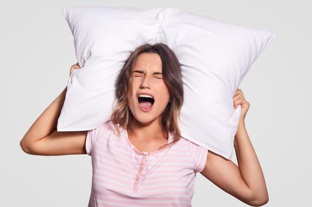 Aantrekkelijke blanke vrouw drukt negatieve gevoelens uit, houdt haar mond wijd open, ogen dicht, draagt een losse pyjama