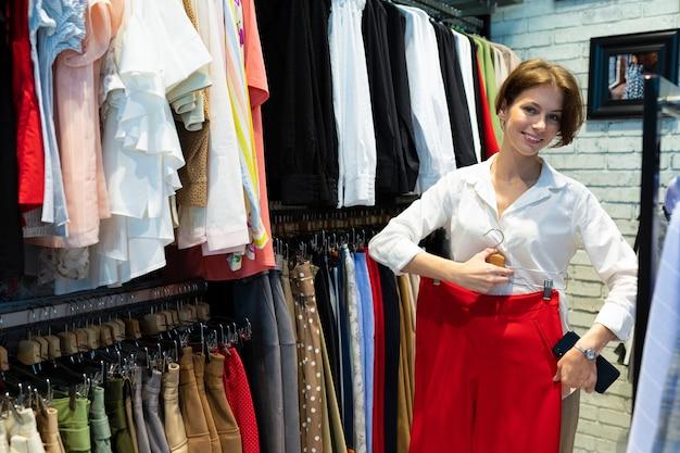 Aantrekkelijke blanke vrouw glimlacht staande met rode rok in haar handen.
