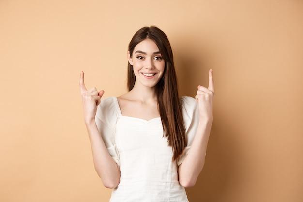 Aantrekkelijke blanke vrouw in jurk vingers omhoog, glimlachen en tonen promo banner, staande op beige achtergrond.