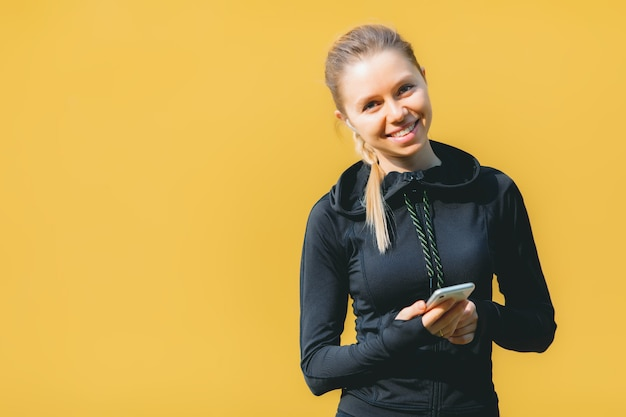 Aantrekkelijke blanke vrouw in sport pak met draadloze koptelefoon met behulp van haar telefoon om muziek op oranje te luisteren