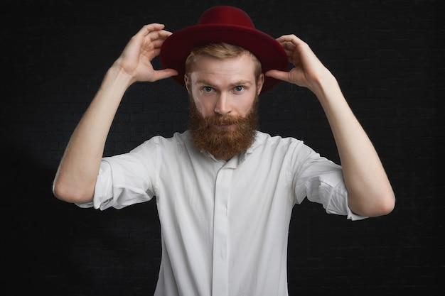 Aantrekkelijke blauwogige jonge kerel met gember bijgesneden baard gaat feesten, stijlvolle rode ronde hoed opzetten. elegante jonge europese man in wit overhemd, zich aankleden, trendy hoofddeksels aantrekken