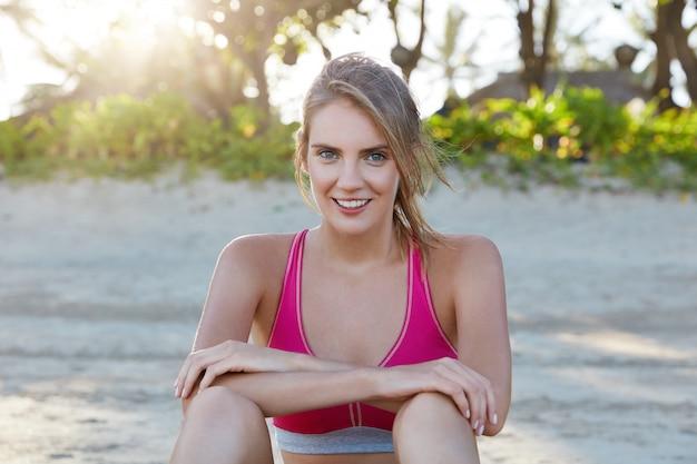 Aantrekkelijke blij vrouwelijke jogger wordt gemotiveerd, heeft ochtendtraining op zandstrand, rust alleen, draagt roze top. sportvrouw die betrokken is bij een actieve levensstijl. mensen, fitness en buitenoefeningen