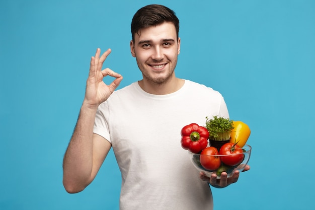 Aantrekkelijke blije jonge klant of chef-kok met het gelukkige glimlach stellen in studio
