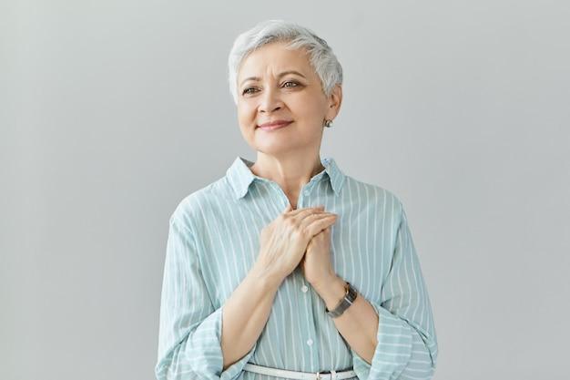 Aantrekkelijke blije vrouw van in de zestig poseren geïsoleerd geraakt door hartdoordringend verhaal of film, kijkend met een tevreden, gelukkige glimlach, hand in hand op de borst. vriendelijkheid en dankbaarheid