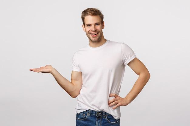 Aantrekkelijke blonde bebaarde man in wit t-shirt met iets op de palm