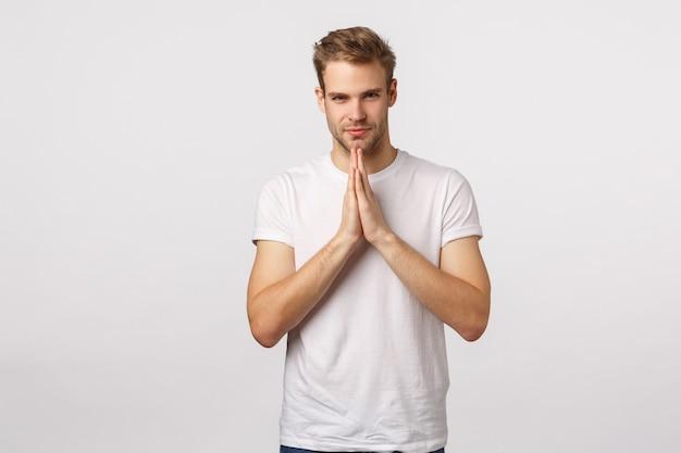 Aantrekkelijke blonde bebaarde man in witte t-shirt bidden