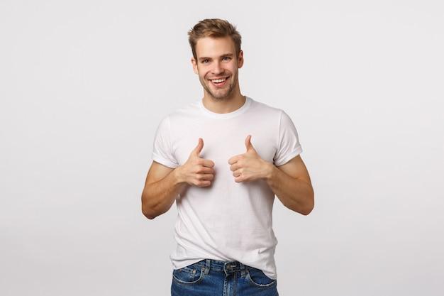 Aantrekkelijke blonde bebaarde man in witte t-shirt geven duimen omhoog