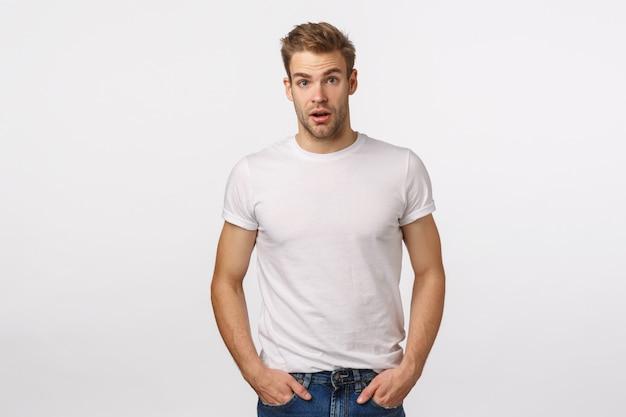 Aantrekkelijke blonde bebaarde man in witte t-shirt poseren