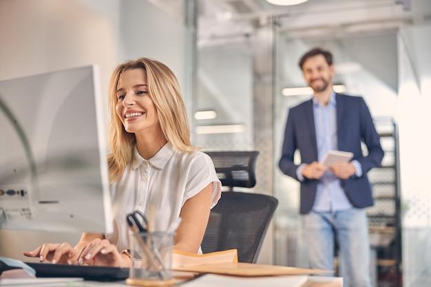 Aantrekkelijke blonde dame die op een desktop-pc werkt en glimlacht terwijl een mannelijke collega achter haar staat