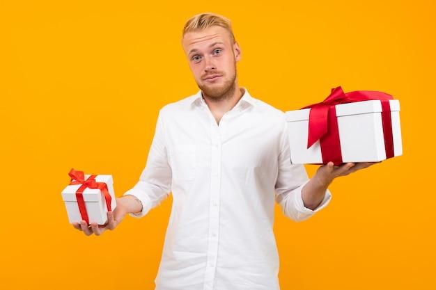 Aantrekkelijke blonde europese jonge man in een wit shirt houdt geschenkdozen op een geel.