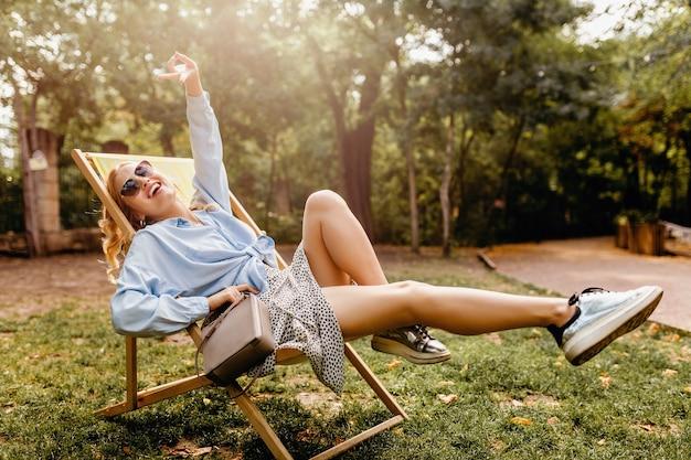 Aantrekkelijke blonde gelukkige vrouw zitten ontspannen in ligstoel in zomer outfit blauw shirt, zilveren sneakers, elegante zonnebril en tas dragen