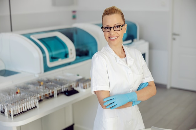 Aantrekkelijke blonde glimlachende laboratoriumassistent die zich in laboratorium met gekruiste handen bevindt.