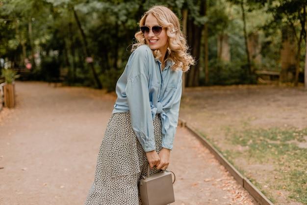 Aantrekkelijke blonde glimlachende vrouw die in park in de zomeroutfit loopt