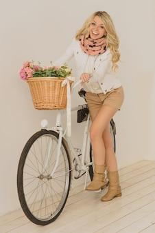 Aantrekkelijke blonde glimlachende vrouw met een witte retro fiets en een mand met bloemen