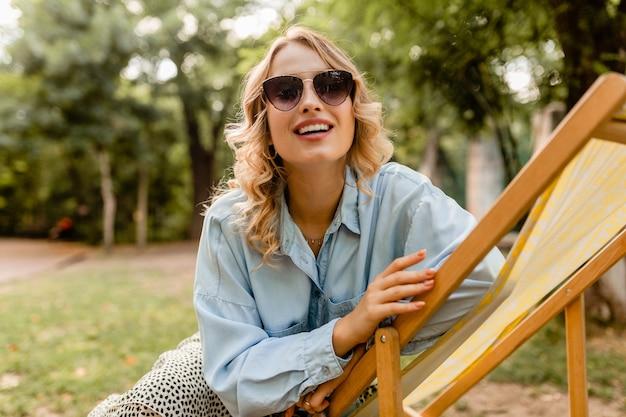 Aantrekkelijke blonde glimlachende vrouw zittend in een ligstoel in een stijlvolle outfit