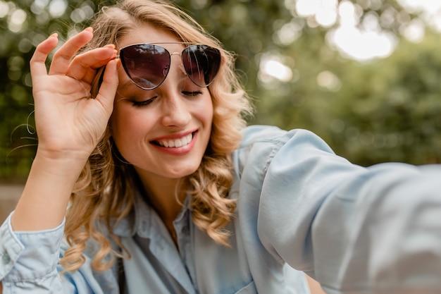 Aantrekkelijke blonde glimlachende witte tandenvrouw die in park in zomeruitrusting lopen die selfiefoto op telefoon neemt