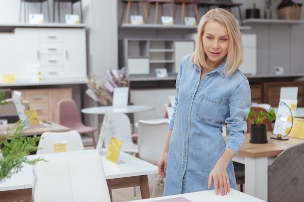 Aantrekkelijke blonde haired vrouw die bij meubilairopslag winkelt, die lijst aangaande verkoop onderzoekt