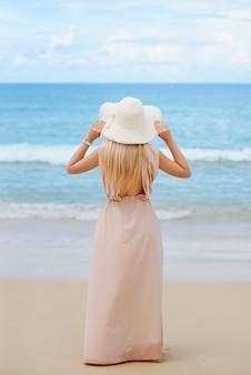 Aantrekkelijke blonde jonge vrouw staat op het witte zand