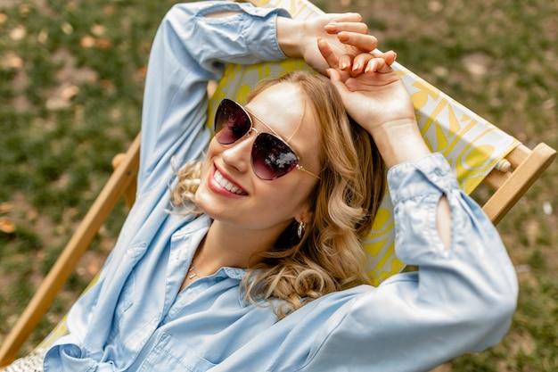 Aantrekkelijke blonde lachende vrouw zit ontspannen in een ligstoel in een stijlvolle outfit