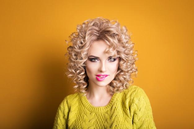 Aantrekkelijke blonde meid. speels uiterlijk. roze lippen. gekruld haar
