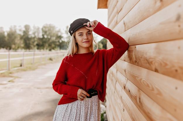 Aantrekkelijke blonde met natuurlijke make-up die er teder uitziet. jonge vrouw in rode trui en stijlvolle hoed poseren in de buurt van het houten huis.