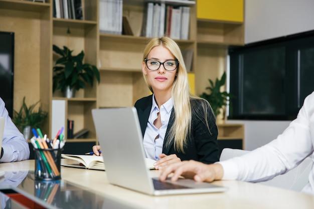 Aantrekkelijke blonde onderneemster die in modern bureau werkt