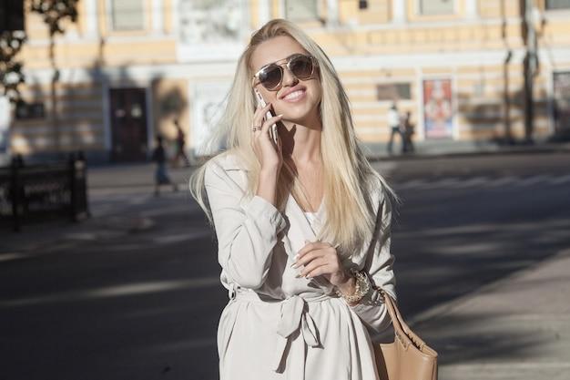 Aantrekkelijke blonde onderneemster die op mobiele telefoon met cliënt spreekt.