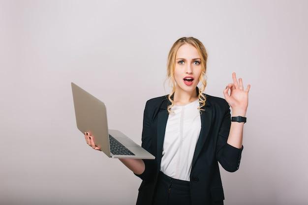 Aantrekkelijke blonde onderneemster met geïsoleerde laptop. kantoorpak dragen, stijlvol, modieus, opgewekt, echte emoties, verbaasd, werknemer, manager