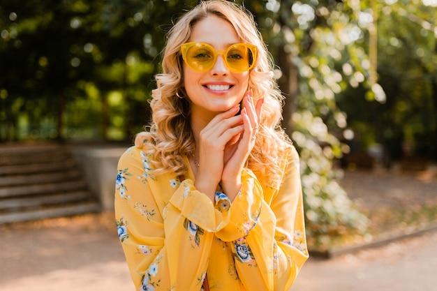 Aantrekkelijke blonde stijlvolle glimlachende vrouw in gele blouse die zonnebril draagt