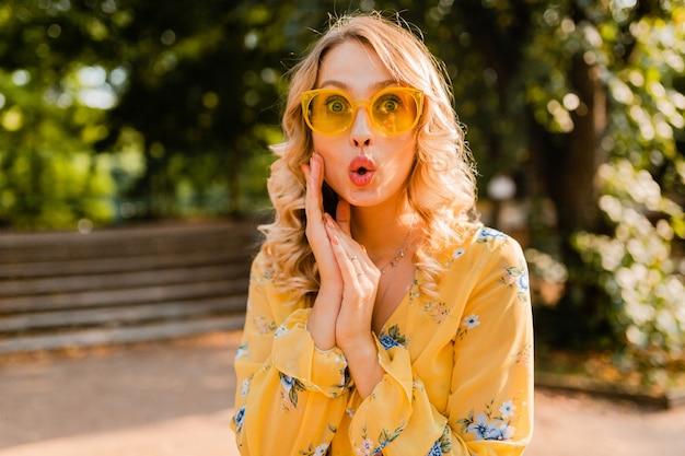 Aantrekkelijke blonde stijlvolle verraste vrouw in gele blouse die zonnebril draagt