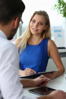 Aantrekkelijke blonde vrouw die aantekeningen maakt tijdens gesprek