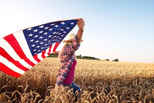 Aantrekkelijke blonde vrouw die door tarweveld loopt en de zwaaiende vlag van de vs houdt