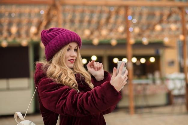 Aantrekkelijke blonde vrouw die een bericht typt op een mobiele telefoon, staande op het plein in kiev
