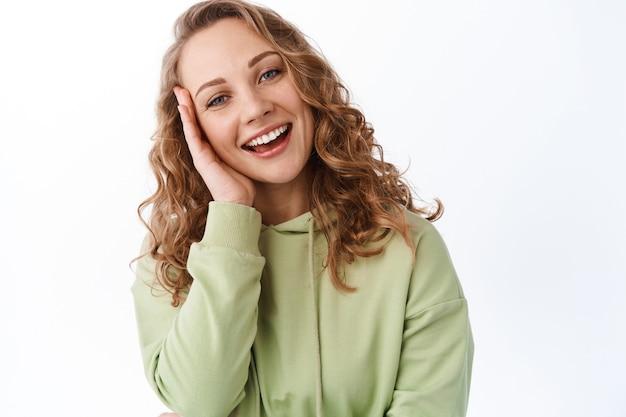Aantrekkelijke blonde vrouw die lacht en een schone, gehydrateerde huid aanraakt met een reinigend effect van huidverzorgingsproducten, staande over een witte muur
