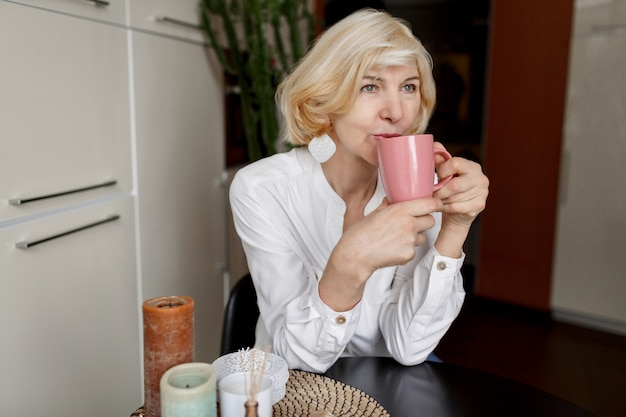 Aantrekkelijke blonde vrouw die op middelbare leeftijd thuis op de keuken ontspannen en koffie drinken