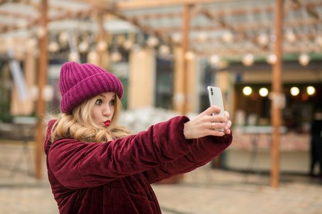 Aantrekkelijke blonde vrouw die plezier heeft en zelfportret maakt op de achtergrond van de slinger in kiev