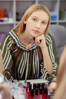 Aantrekkelijke blonde vrouw die voor de spiegel zit terwijl ze aan haar uiterlijk denkt