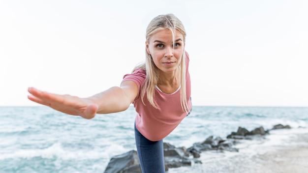 Aantrekkelijke blonde vrouw doet yoga buitenshuis
