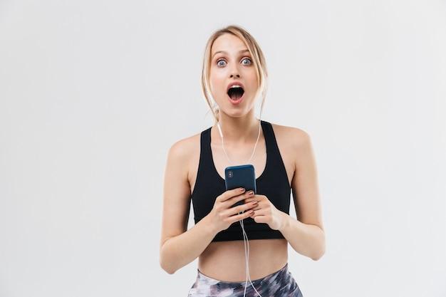 Aantrekkelijke blonde vrouw gekleed in sportkleding trainen en luisteren naar muziek met smartphone tijdens fitness in sportschool geïsoleerd over witte muur