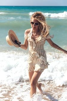Aantrekkelijke blonde vrouw in gestreepte jurk koelen op de zee