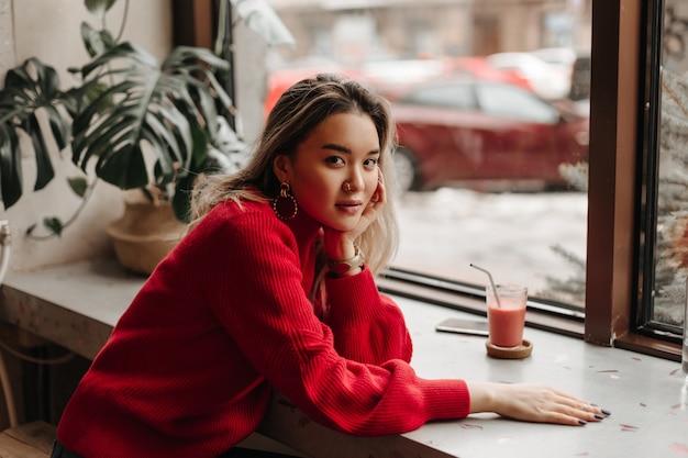 Aantrekkelijke blonde vrouw in oversized lichte trui leunde op tafel en kijkt naar voren tegen raam