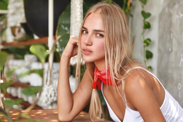 Aantrekkelijke blonde vrouw met ernstige uitdrukking, nonchalant gekleed, zit alleen in gezellig café