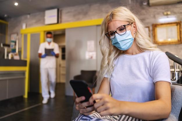 Aantrekkelijke blonde vrouw met gezichtsmasker zitten in het ziekenhuis, met behulp van mobiele telefoon en wachten om te worden gebeld door een arts.