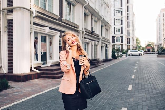 Aantrekkelijke blonde vrouw met lang haar loopt rond britse wijk. ze draagt een zwarte jurk, houdt koffie vast en spreekt aan de telefoon