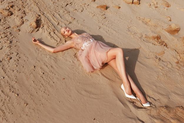 Aantrekkelijke blonde vrouw poseren in borduurjurk op woestijn, liggend op gouden zand, bij het licht van de zonsondergang.
